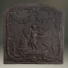 Late 17th century Flemish cast iron fireback with a cupid holding a torch standing in foliage.