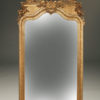 Ornate French beveled mirror with gilded frame depicting cherubs, birds and urn