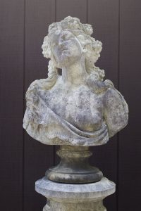 English cast limestone bust of a Bacchante atop a column.