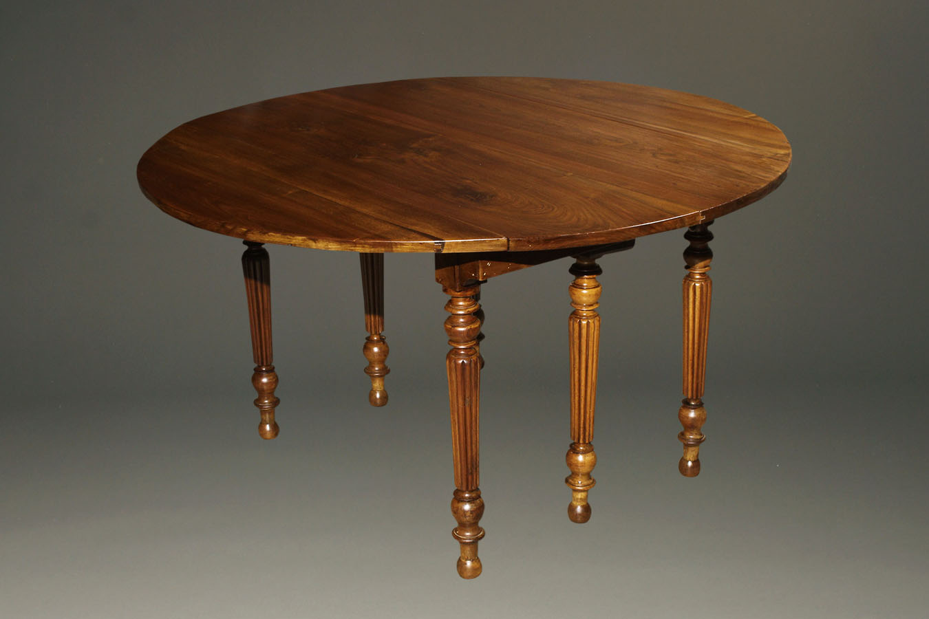 19th century French walnut kitchen table with drop leaves and fluted legs.